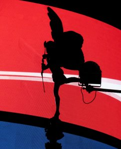 The statue of Eros at Piccadilly Circus, silhouetted against the electronic advertising hoardings...