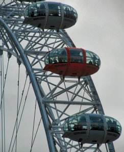 Capsules on the London Eye, one red, on London's South Bank...